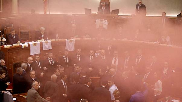 Albania's opposition lawmakers throw smoke bombs inside the Parliament