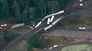 Vagones del tren descarrilado colgando sobre la autopista