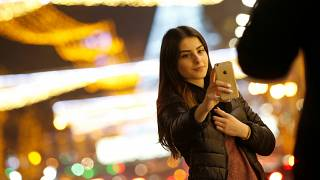 A woman takes a selfie on a street with Christmas decoration in Tbilisi, Ge