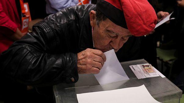 Mann mit traditioneller katalanischen Mütze küsst seinen Stimmzettel