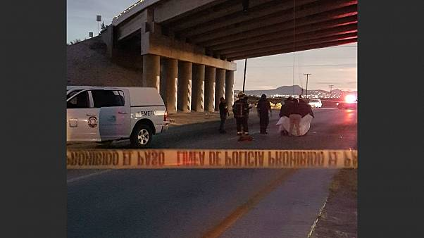 Rescuers attend to bodies that were hanged on the freeway to La Paz