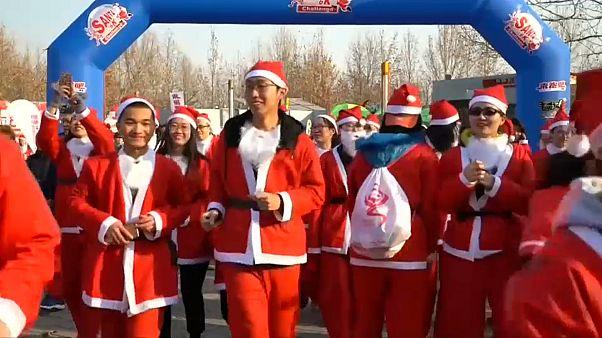 Chinesische Weihnachtsmänner rennen durch Park