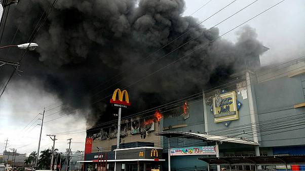 Smoke billows from a shopping mall on fire in Davao City