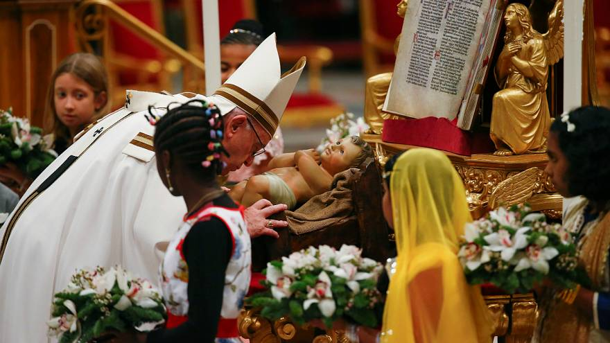 Pope Francis kisses a statuette of baby Jesus