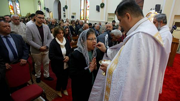 Iraqi Christian receive holy communion during a mass on Christmas