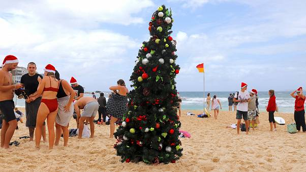 Festive revellers brave the cold and strip down to their bikinis to spend Christmas on the beach