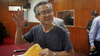 FILE PHOTO: Alberto Fujimori waves to the media in court