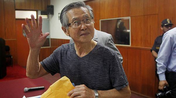 FILE PHOTO: Alberto Fujimori waves to the media in court