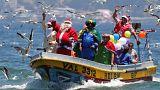 Un hombre vestido con un traje de Papa Noel saluda a la gente desde el bote