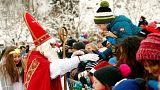 A Santa Claus waves to children