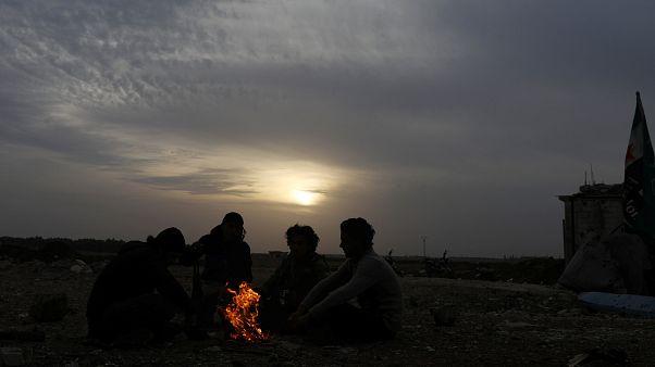 Rebeldes sírios sentados junto a uma fogueira na região de Dael