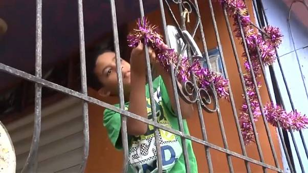 Un niño coloca una guirnalda de Navidad en las rejas de una ventana