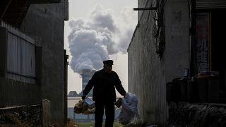 Kínai szemétgyűjtő férfi, háttérben egy kerámiagyár