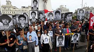 People holding pictures of victims of the guerrilla conflict