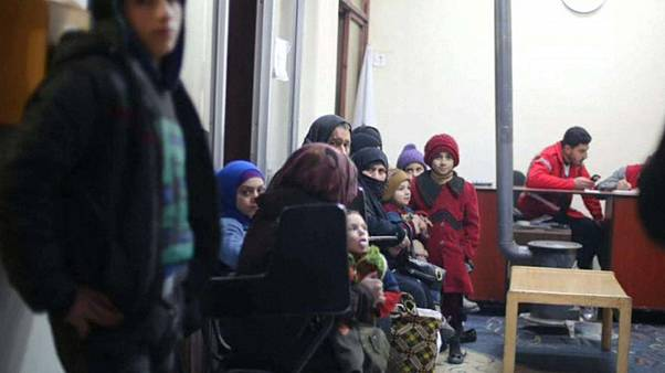 Children and families wait to be evacuated