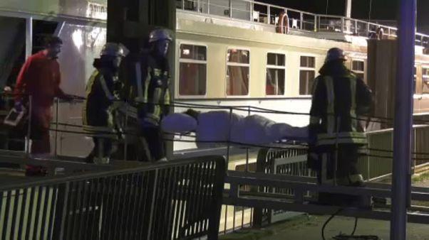 Rettungskräfte bringen einen verletzten Passagier von Bord.