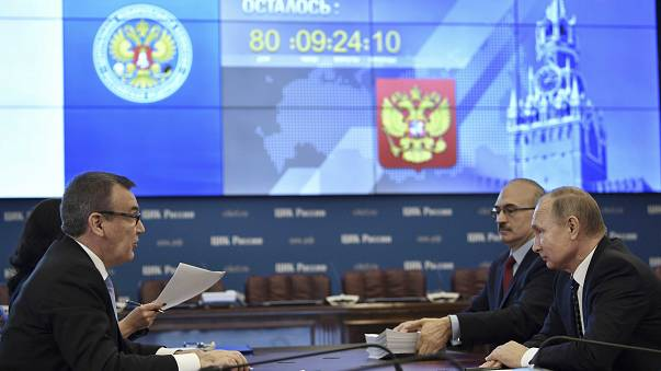 Russian President Vladimir Putin (R) visits the Central Election Commission