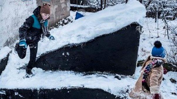 Anya, 13, plays with her sister in Avdiivka, eastern Ukraine