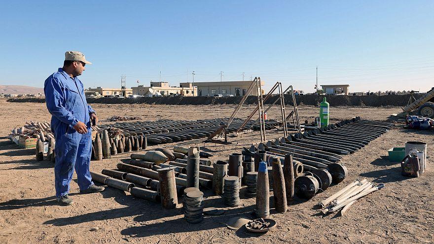 Az iraki hadsereg egyik katonája elkobzott lőszereket néz Moszul határában