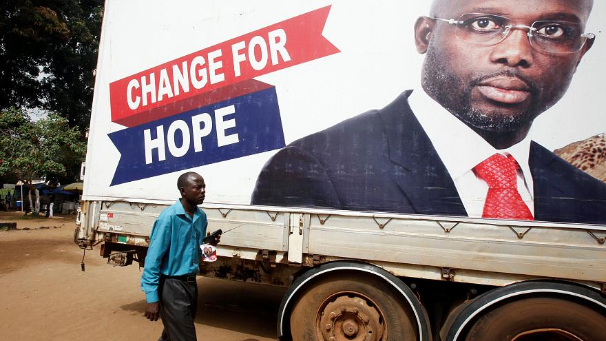 A supporter of George Weah listens to the announcement of the presidential