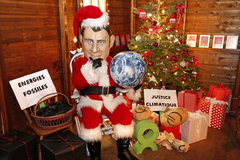 Un attivista Oxfam vestito da Macron-Santa Claus