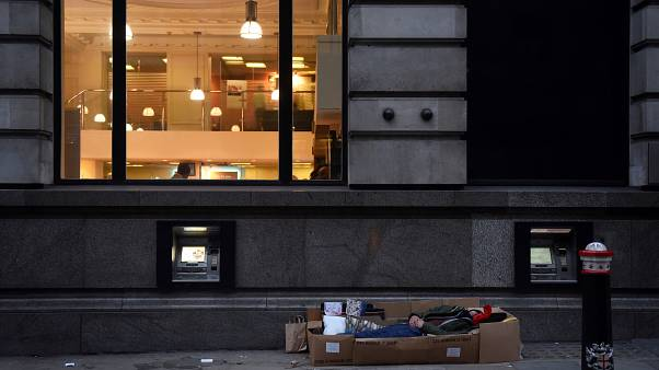 A homeless man sleeps in the cardboard box where he lives, outside Barclays