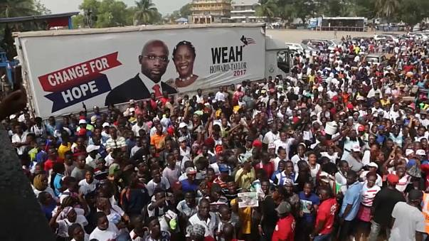 Crowds gather around a George Weah campaign poster ahead of his arrival