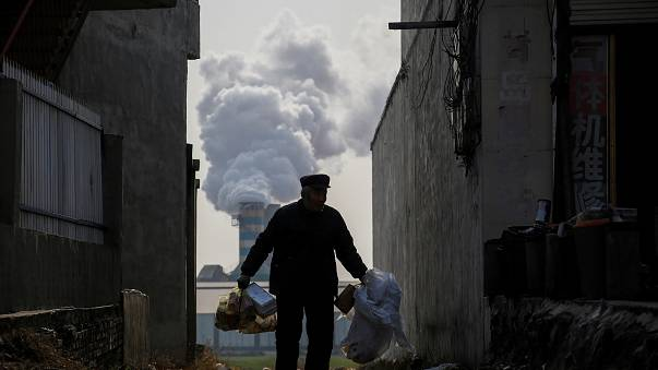 A man collects recyclables as smoke billows from a factory in Gaoyi, China