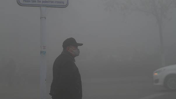 A man wearing a mask stands amid heavy fog in Jinan, Shandong province
