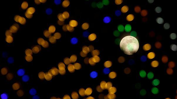 The 'supermoon' full moon is seen through Christmas lights in Valletta