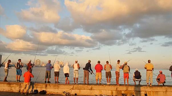 People fish along Havana's Malecon seafront.