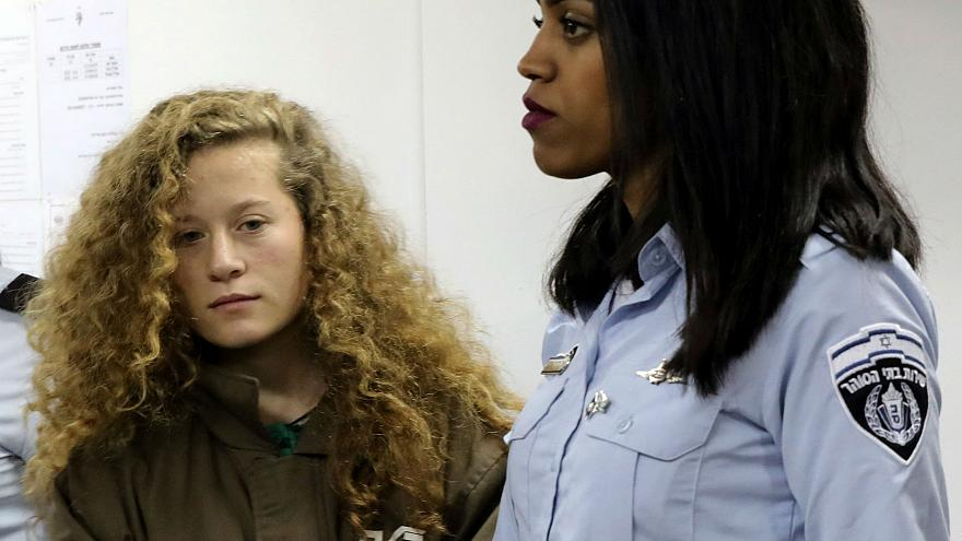 Palestinian teen Ahed Tamimi in court escorted by Israeli prison officer
