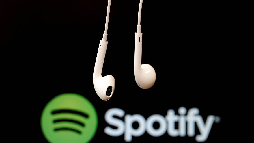 Headphones are seen in front of a logo of online music streaming service