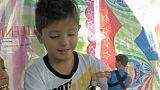 Niño juega con un juguete donado en una tienda de campaña