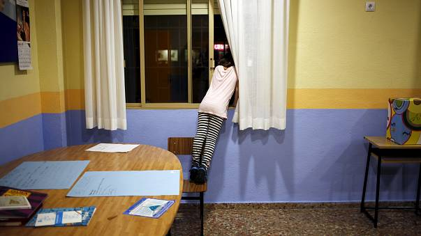 A girl looks at out at a street through a window while attending a program