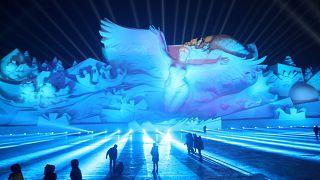 Des visiteurs admirent une gigantesque sculpture de glace à Harbin (Chine)