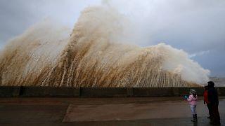 Walkers watch the waves breaking in New Brighton in Britain.