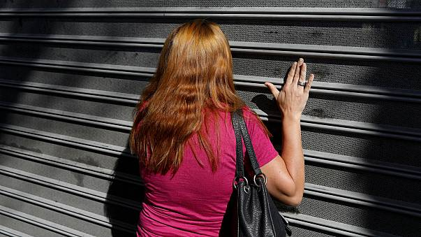 A woman bangs on the gates of a supermarket in Caracas, Jan 6