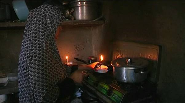A Gaza resident cooks by candlelight