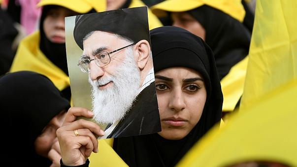 A woman carries a picture of Iran's Supreme Leader Ayatollah Ali Khamenei a
