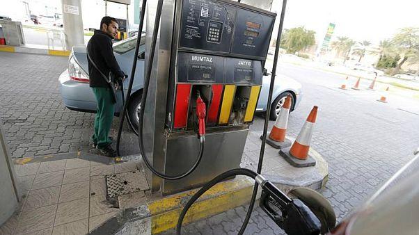 عامل يزود سيارة بالبنزين في محطة وقود بالمنامة