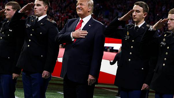 Trump stands with ROTC students to participate in the national anthem