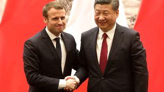 French President Emmanuel Macron (L) and Chinese President Xi Jinping shake