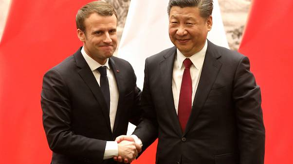 French President Emmanuel Macron (L) and Chinese President Xi Jinping shake