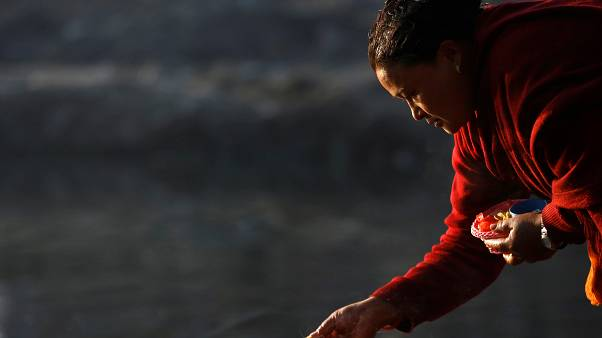 A devotee offers prayer along the bank of Hanumante River