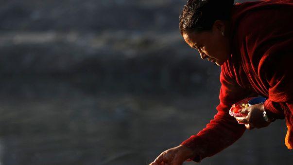 A devotee offers prayer along the bank of Hanumante River