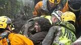 Emergency personnel carry a woman rescued from a collapsed house in USA