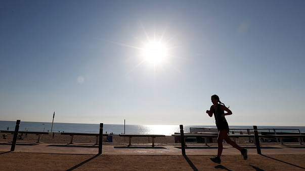 A woman exercises on a hot day in Barceloneta beach in Barcelona, Spain.