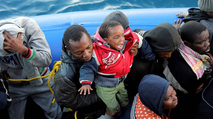 Migrants in a dinghy are rescued by Libyan coast guards