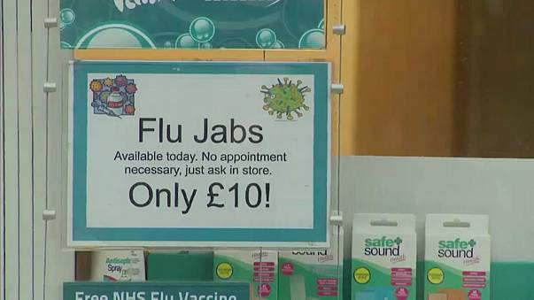 A sign in a shop window advertises the Flu vaccine